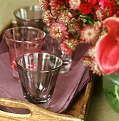 Empty water glasses on a wooden tray