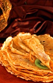 Pile of crepes with icing sugar, slice of kiwi, orange peel