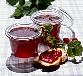 Raspberry jelly in jars and on slice of bread