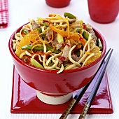 Asian noodles with pork, vegetables and oranges
