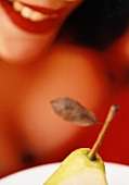 Pear in front of woman with red lips (close-up)