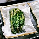 Grüner Spargel mit Kräuterbutter in der Papierhülle gebacken