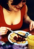 Woman eating waffles with cherry compote