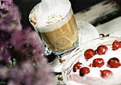 Glass of latte macchiato and quark dessert with cherries