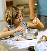 Baking scene: a little girl cracking an egg