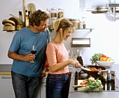 Kitchen scene: woman at cooker, man beside it with wine glass