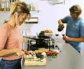 Kitchen scene: woman cutting courgette, man pouring wine