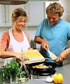 Man and woman at cooker with pan of vegetables