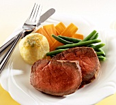 Two slices of roast beef with a dumpling and vegetables