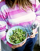 Woman holding dish of rocket salad with pine nuts
