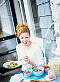 Woman at terrace table with tomato quiche, melon salad on side