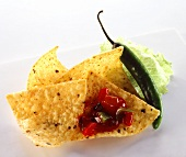Taco chips with red chili sauce, green chili pepper beside them
