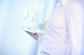 Woman carrying tray of champagne glasses (close-up)