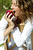 Young woman biting into a red apple