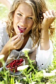 Young woman in grass with a bowl of wild strawberries