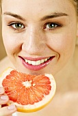 Young woman with a slice of blood orange
