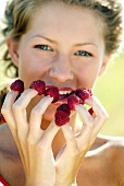 Young woman with raspberries on her finger tips
