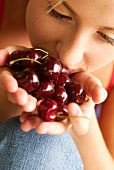 Young woman holding cherries in her hands
