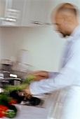 Mann wäscht Gemüse und Salat im Küchespülbecken