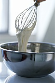Egg whisk with sponge mix over a metal bowl