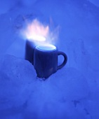 Two small mugs of burning schnapps in snow
