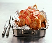 Whole roast chicken with bacon in roasting dish