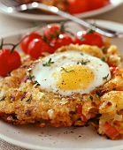 Fried egg on potato rosti with bacon, with vine tomatoes