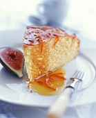 Piece of rich sponge cake with orange sauce; half a fig
