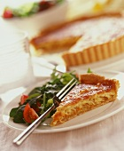 Piece of cheese and onion quiche with rocket salad