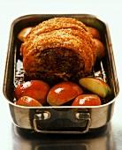 Roast pork roll with crackling on apple quarters