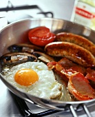 English breakfast: fried egg, sausage, bacon and tomato