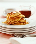 Eight pancakes with maple syrup on a pile of plates