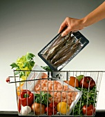 Hand placing packed fish into shopping basket of shopping