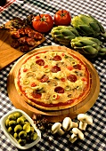 Pizza with salami, artichokes, olives and tomatoes; ingredients