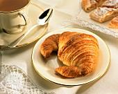 Croissant auf einem Teller mit Goldrand