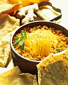 Red lentils with slices of mango, with poppadoms (India)