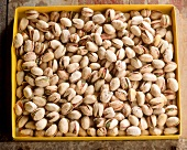 Roasted and salted pistachios in a yellow cardboard box