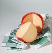 Whole Edam cheese, with piece cut off, on kitchen cloth