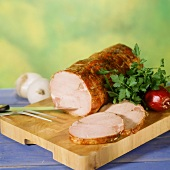 Cold roast pork roll on wooden board, carved