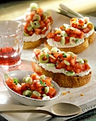 Slices of white bread with soft cheese and diced tomatoes