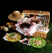 Picnic basket with food, sun hat