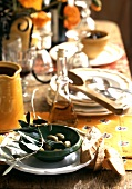 Table laid in country house style, bowl of olives, bread