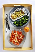 Sole cooked in foil, broccoli and tomato salad on tray