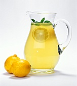 Glass jug of lemonade, lemons beside it
