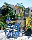 Blauer Tisch mit Holzstühlen auf der Terrasse eines griechischen Gartenlokals