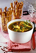 Chicken soup with vegetables, bread sticks in glasses behind
