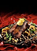 Christmas goose on bed of chestnuts with slices of fruit