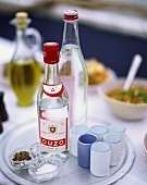 Two bottles of Ouzo on tray with glasses, salt and pepper