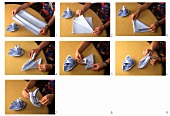 Folding blue fabric napkins into napkin boats