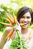 Woman with a bunch of carrots biting into one of them